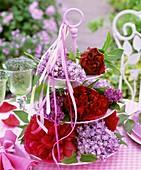 Blüten von Pfingstrosen und Flieder auf Etagere mit Bändern