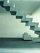 An armchair under a flight of stairs