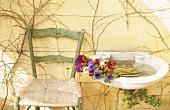 Blumenstrauß in einem alten Waschbecken neben Stuhl
