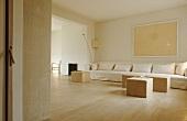 Schlichtes Wohnzimmer in Naturfarben gehalten mit langem Sofa und Sitzhocker auf Parkettboden