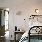 Altes Schlafzimmer mit Leselampe an der Wand befestigt und schmiedeeisernes Bettgestell