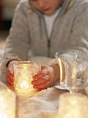 Junge hält ein Glas mit einer brennenden Kerze