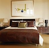 Ein Doppelbett mit Brauner Wildlederdecke am Bettende und passende Nachttischkonsolen mit Leselampen