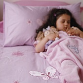 Girl asleep in bed with a doll