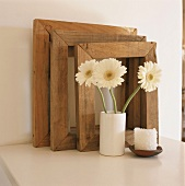 Three wooden picture frames and vase of gerbera daisies