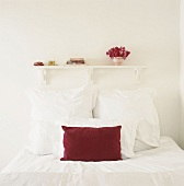 Einzelbett mit weißer Bettwäsche und einem roten Kissen unter kleines Bücherregal