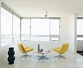 Two easy chairs and a table in a room with large windows