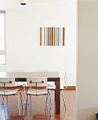 Ein massiver Holztisch und weiße Designerstühle im hellen Essraum