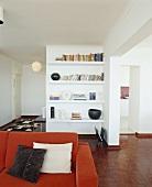 Blick auf ein Bücherregal hinter einer roten Couch