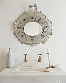 A wash basin with an ornately decorated mirror