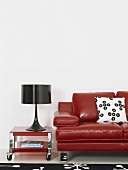 A red leather couch with black table lamp