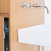 Nahaufnahme eines Waschbeckens vor Installationsschacht aus Holz mit Stauraum