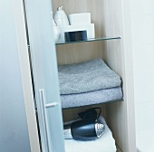 Towels and hair drier on shelves in a cupboard