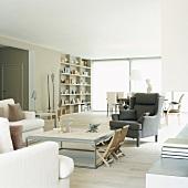 Helles, großräumiges Wohnzimmer mit Wandregal im Hintergrund und mit kleinen Klappstühlen am Couchtisch