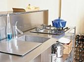 Edelstahl-Küchenelement mit bedeckbarem Spülbecken und einem direkt daneben angebrachten Gasherd