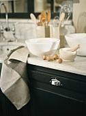 Porzellanschalen und Porzellanmörser mit Holzstößel auf einer Arbeitsfläche aus hellem Marmor; daneben frische Pilze
