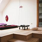 Raum im asiatischen Stil, mit Holzdielen, Bodenkissen, Teetisch und Futonmatratze