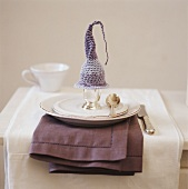 Place setting with boiled egg under a crocheted egg cosy
