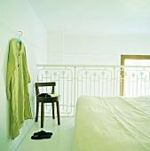Doppelbett auf Galerie mit weißem Geländer; an der Wand hängt ein Kleidungsstück am Kleiderbügel