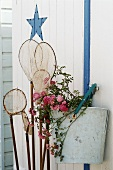 Landing net and flowers hanging on a wall