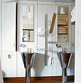 Zwei Standwaschbecken aus Edelstahl in Badezimmer mit weisser Holzwand