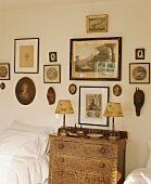 Antique chest of drawers between twin beds below collection of antique pictures