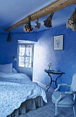 Blue bedroom with dried flowers hanging from ceiling beams; floral, quilted counterpane on double bed