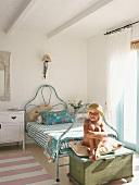 Little girl sitting on trunk in bedroom