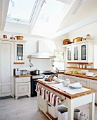 White, nostalgic, country-house kitchen with large skylights in sloping ceiling