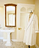 White dressing gown on tailor's dummy in nostalgic bathroom with pedestal sink and large, wood-framed mirror