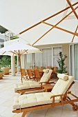 Sun terrace with square, white awning, wooden lounger, dining table and folding chairs