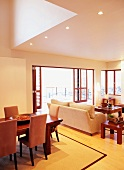 Cheerful interior with dining and living area and open terrace doors leading to terrace