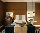 Bedroom in shades of brown with striped headboard and antique chest of drawers