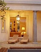 Überdachte Terrasse mit imposanten Säulen im klassisch-dorischen Stil, einem Kieselsteinboden und Holzliegen