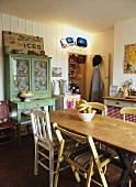 Ländliches, einfaches Esszimmer mit schlichtem Holztisch, Einzelstücke vom Trödel und einer Vorratskammer