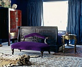 Exquisite furniture in bedroom with heavy blue curtains, silk rugs and tiger-skin rug with head