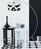 Arrangement of black and white arc lamp, stools, cushion, flooring and wallpaper