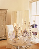 Magnificent silver candelabras and ornamental fruit on round table with metal base