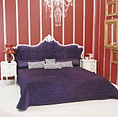 Chandelier above majestic, purple double bed framed by red and white striped wallpaper and collection of gilt picture frames