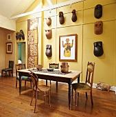 Esszimmertisch vor gelbe Wand mit afrikanischen Skulpturen und Masken