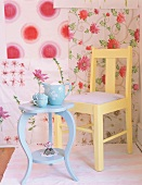 Chair and table in front of floral wallpaper