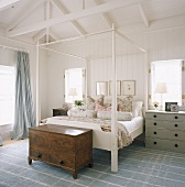 Holzkommode am Bettende eines Himmelbettes im Schlafzimmer