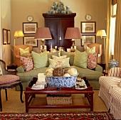 Symmetrisch eingerichtetes Wohnzimmer mit grüner Couch und und rosane Sessel im amerikanischen Stil