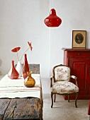 Ein rustikaler Holzstamm als Esstisch im Essraum mit roter Kommode und geblümter Sessel