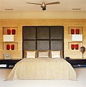 Schlafzimmer mit großem Doppelbett und Lederkopfteil vor Holzwand mit eingebauten Nischen