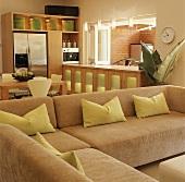 L-förmiges Sofa mit grünen Kissen vor Einbauhüche mit Durchreiche zu einer Loggia
