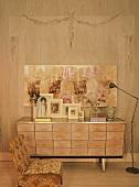 Holzkommode mit vielen Schubladen und Familienfotos vor rustikale Wand mit zeitgenössischem Gemälde
