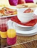 Glasses of juice and half grapefruit in bowl