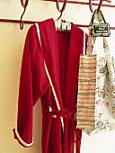 Roter Bademantel und Tasche mit Blumenmuster an der Garderobe