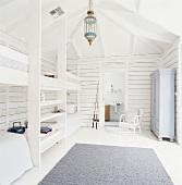 Kinderzimmer im weiß lackiertem Dachgeschoss mit Holzbalken und Hochbetten